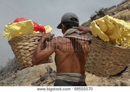 KAWAH IJEN, INDONESIA - AUGUST 8, 2011: Miner carries baskets with sulphur in fumes of toxic volcanic gas from sulphur mines in the crater of the active volcano of Kawah Ijen, East Java, Indonesia.