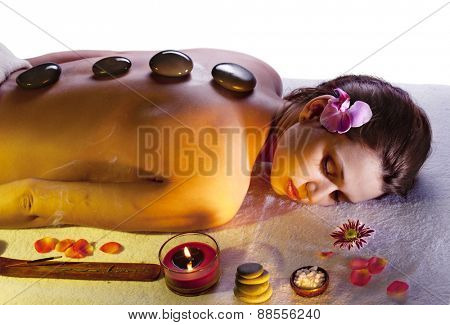 Young woman getting stone massage procedure.