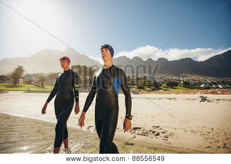 Young Triathletes Walking Into The Sea Wearing Wetsuit