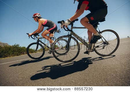Cyclist Riding Bicycles Down Hill On Country Road