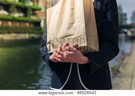 Woman With Paper Bag By Canal