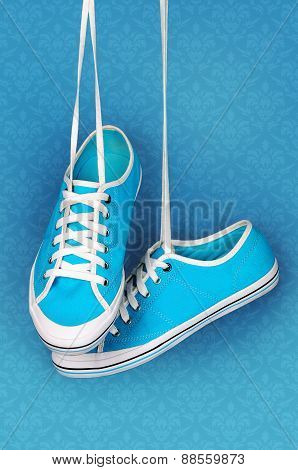 Pair Of Turquoise Sneakers Hangs On The Laces.