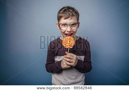 boy teenager European appearance in sunglasses licks colorful ca