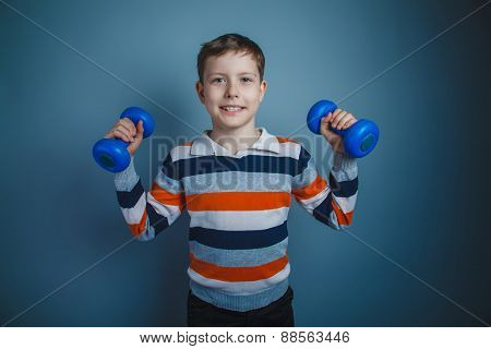 teenager boy brown European appearance holds a blue dumbbell on