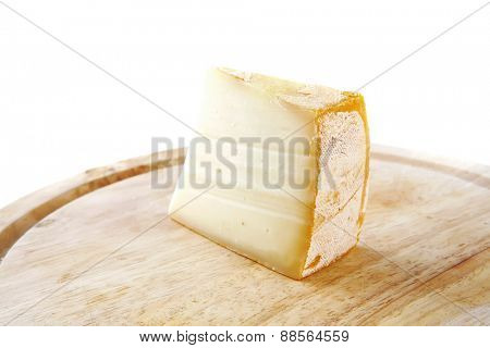 piece of light swiss cheese on wooden board