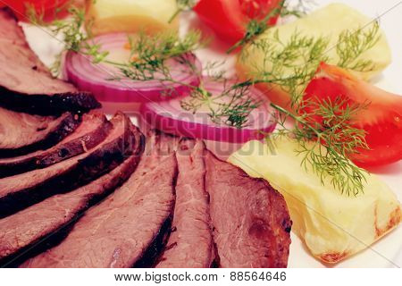 grilled beef meat steak with fried potatoes and tomatoes on white plate