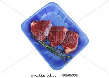 uncooked raw beef fillet with thyme twig on blue tray isolated over white background