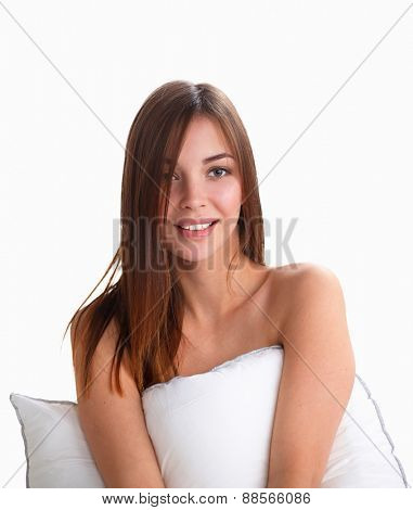 Young woman holding a pillow while sitting on her bed.