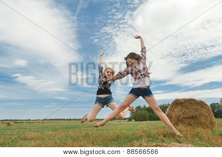 Blonde and brunette girls leaping through air for fun