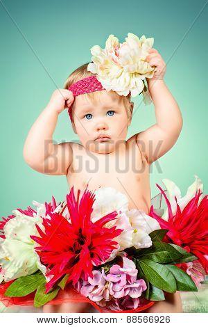 Sweet little baby girl sitting among flowers. Beauty, childhood. Healthcare.