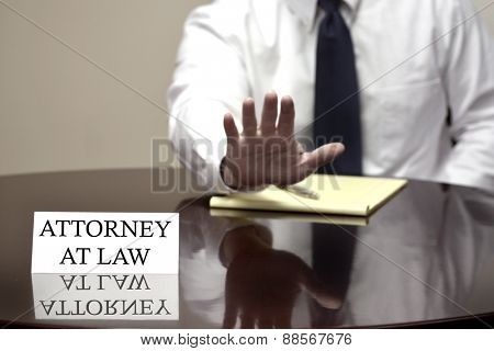 Attorney at Law sitting at desk with hand up to stop deal or talking negotiation
