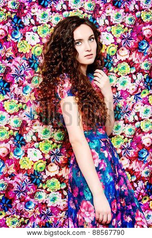 Beautiful tender woman in bright summer dress over floral background. Beauty, fashion.