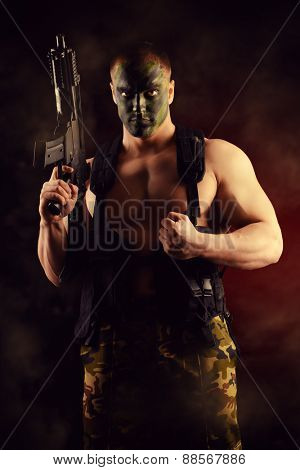 A soldier in war paint holding the automatic rifles. Military, war. Special forces.
