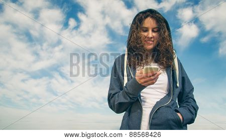 Young woman with hoodie and sportswear looking smartphone
