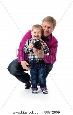 Father And Young Son With A Camera In His Hands.