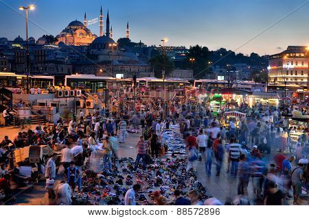 People rest and socialize in a square near Galata Bridge, Istanbul, in Turkey.