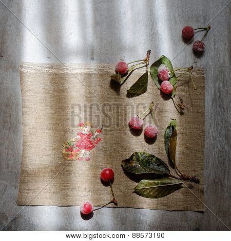 Red Box , Embroidery And Frozen Cherries On A Wooden Gray Background