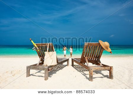 Couple in white walking on a tropical beach at Maldives