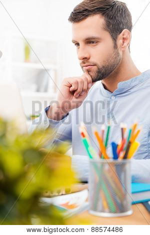 Concentrated On Work. Handsome Young Man In Shirt Working On Laptop And Holding Hand On Chin While S