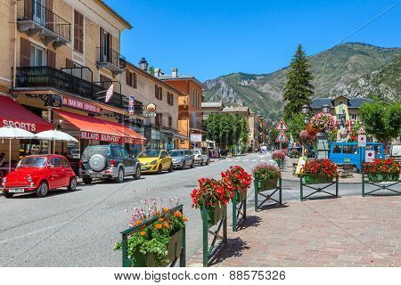 TENDE, FRANCE - AUGUST 12, 2014: Restaurants and bars along narrow road through Tende - small tourist town in French Alps, located on old route of salt trade and known for its cheese, honey and jams.
