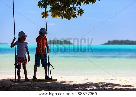 Kids having fun swinging at beach on summer vacation