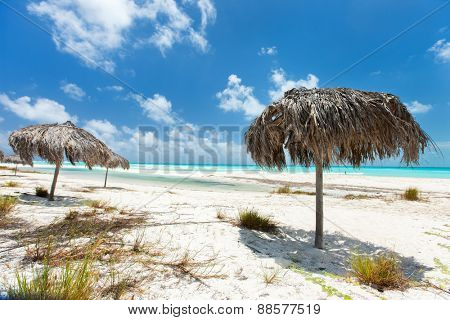 Tropical thatch umbrellas on a beautiful Caribbean beach in Cuba