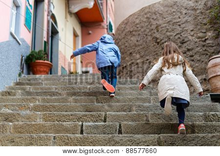 Kids running upstairs at street of colorful Manarola village, Cinque Terre, Italy