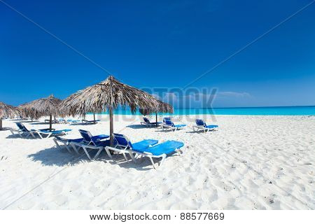 Tropical thatch umbrellas on a beautiful Caribbean beach in Cuba