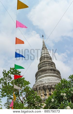 ancient stupa with tree and colorful flag