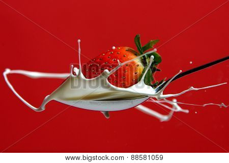 Strawberry on the purple spoon and milk splash