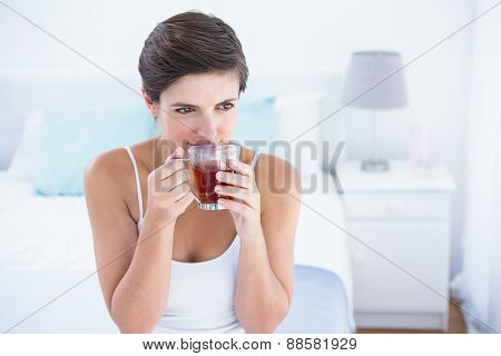 Thoughtful woman drinking cup of tea at home in the bedroom