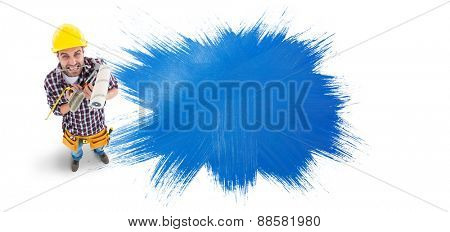 Frustrated handyman holding various tools against blue paint