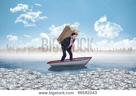 Businessman carrying bag of dollars against small boat in the sea with city on horizon