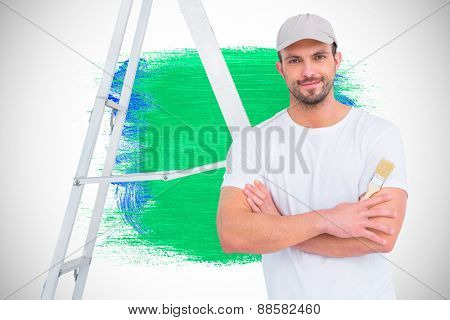 handyman with paintbrush and ladder against blue and green paint