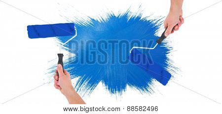 Handyman holding paint roller against blue paint