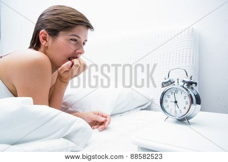 Thoughtful young woman lying in bed at home in the bedroom