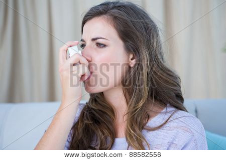 Pretty woman taking her inhaler at home at the living room