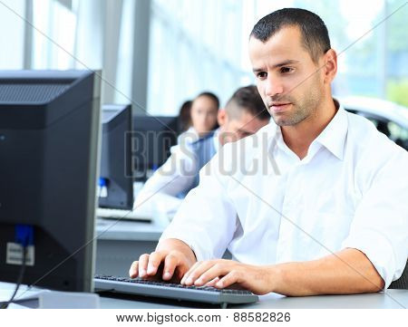 Casual businessman using laptop in office, sitting at desk, typing on keyboard