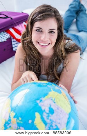 Beautiful woman with a suitcase pointing on a globe at home in the bedroom