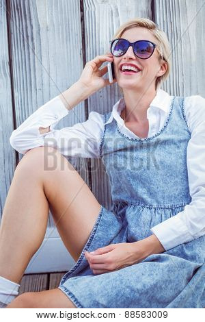 Pretty blonde woman wearing sun glasses and calling on the phone on wooden background