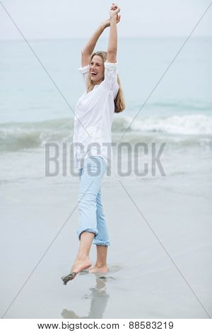 Smiling blonde having fun by the sea at the beach