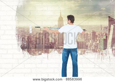 Man using paint roller on white background against room with large window looking on city