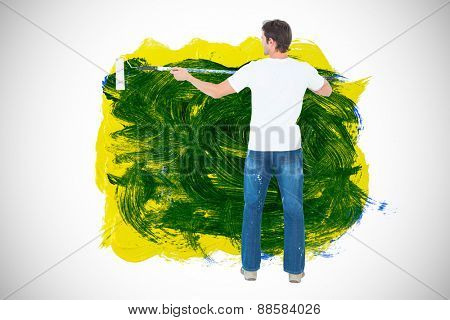 Man using paint roller on white background against blue and yellow paint making green