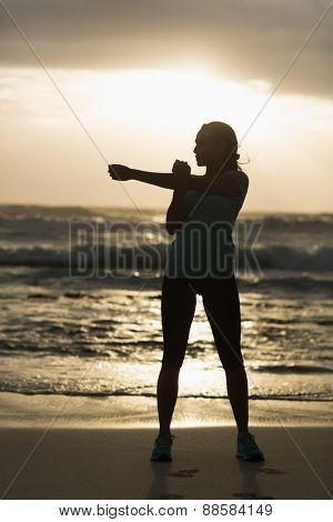 Sporty brunette stretching on the beach in the evening