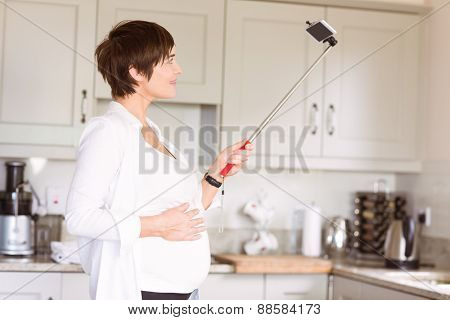 Pregnant woman taking a selfie at home in the kitchen
