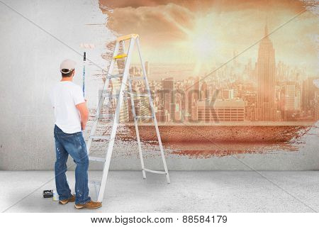 Handyman with paint roller and ladder against sun shining over city