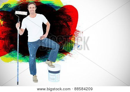 Man with paint bucket and roller on white background against red green black yellow and blue paint