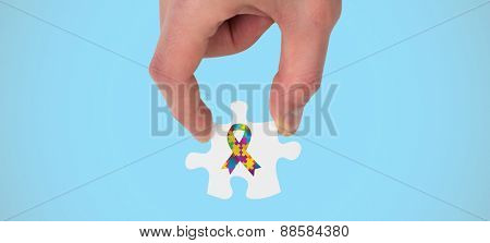 Hand holding jigsaw piece against blue background with vignette