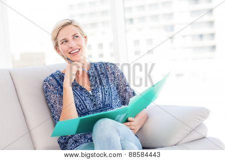 Pretty blonde woman taking notes on the couch in the living room