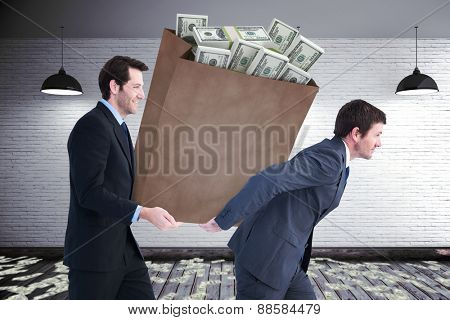 Businessmen carrying bag of dollars against grey room